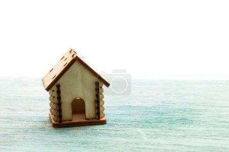 Photo pour Maison en bois de modèle de jouet comme famille de symbole et concept d'amour sur le vieux fond en bois bleu ensoleillé achetant une maison, hypothèque, réparation, stabilité - image libre de droit