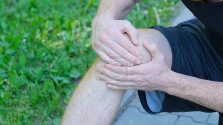 Photo for Male athlete runner touching foot in pain due to sprained ankle. unrecognizable athlete sits on the ground and suffers from knee pain. - Royalty Free Image