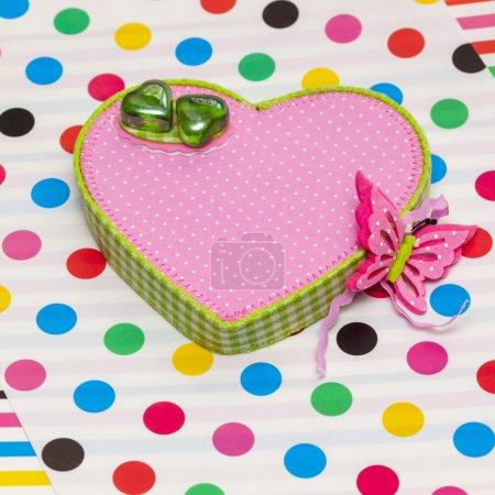 Photo pour Il y a deux coeurs en verre vert sur la boîte rose avec papillon - image libre de droit