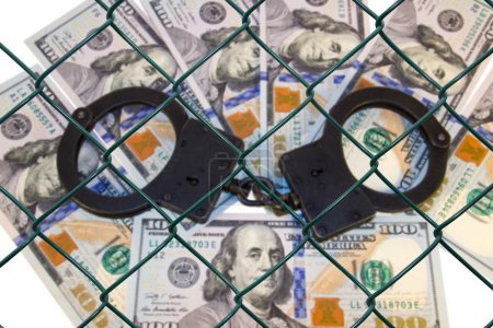 Metal handcuffs on the background of dollars under wire netting (lattice)