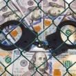 Handcuffs on the background of dollars under wire netting (lattice)