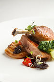 Dobře opečené a křupavé kachní confit s pečené fenykl, citrusové plody a prořezávat omáčkou. Pečené kachní stehno. Bílé nádobí