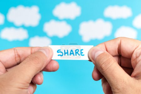 Share ideas. Two hand holding a paper showing the word share on blue background with clouds