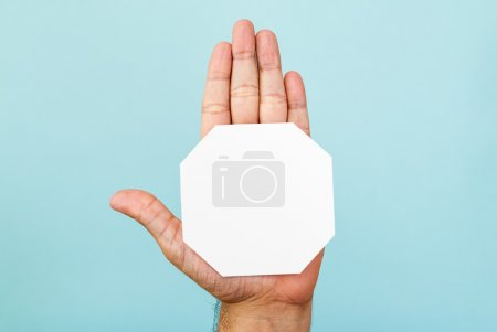 Stop hand and octagon shape on blue background
