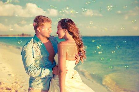 Photo pour Heureux jeunes mariés sur le littoral tropical avec des bulles de savon - image libre de droit