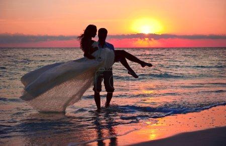 romantic newlyweds on beach