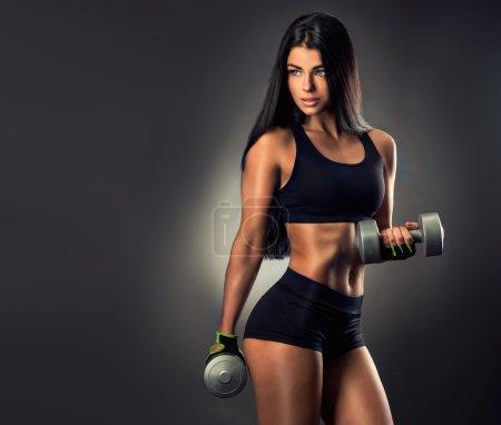 Beautiful fitness woman lifting dumbbells