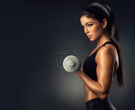 Beautiful fitness woman lifting dumbbell