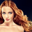 Beautiful model with long curly red hair.  Styling...