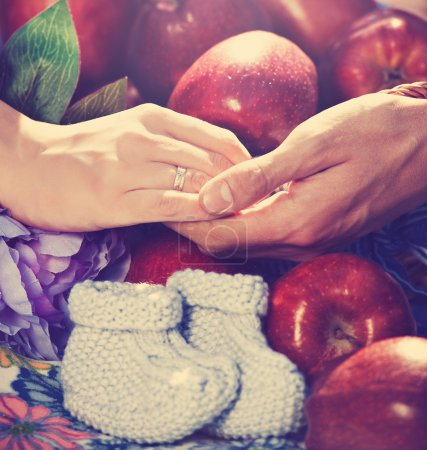 hands over red apples with baby booties