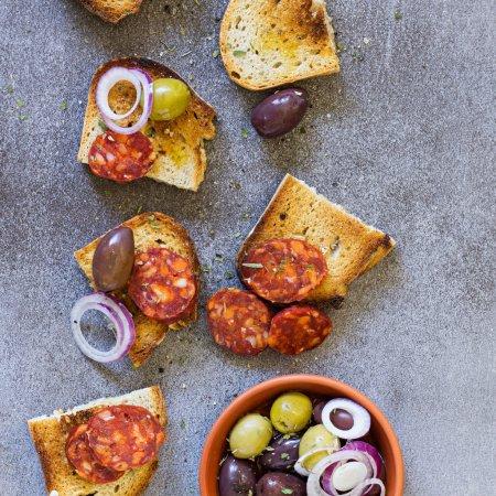 Photo pour Tapas traditionnels espagnols. Pain au chorizo et aux olives . - image libre de droit