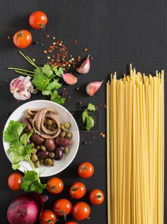 Photo for Pasta Puttanesca Ingredients on dark background - Royalty Free Image