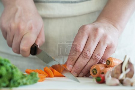 Photo for Chef Chopping Carrots on Wooden Chopping Board - Royalty Free Image