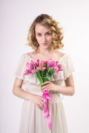 Beautiful blonde spring girl with flowers