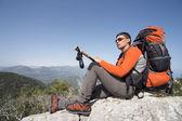 Mladý muž s batohem na vrcholu hory za slunečného dne