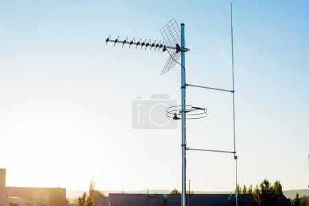 simple antenna mast with antennas to receive digital TV and radio signals, DVB-T, DVB-T2 and FM (horizontal polarization) including delayed lightning rod. In the background the peaks of roofs.