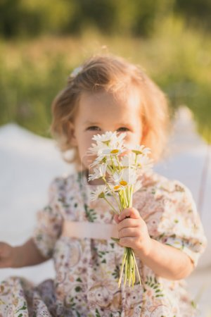 Little girl smelling a daisy