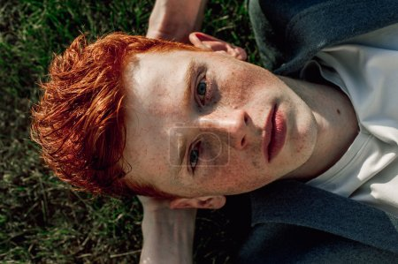 Portrait of attractive stylish young guy model with red hair and freckles sitting on green grass, wearing jacket. Fashionable outdoor shot