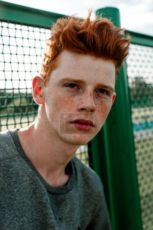 One young handsome red haired fashionable boy standing near stadium in sunny day outdoor , wearing casual clothing