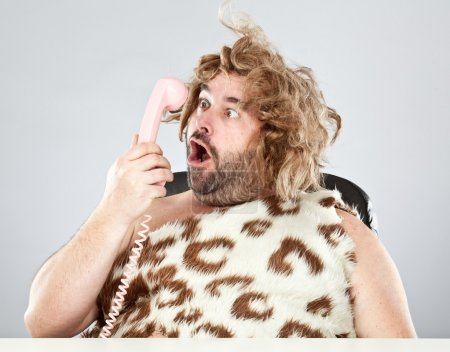 ugly rude prehistoric man talking on the phone