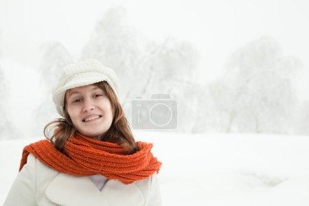 Photo pour Belle femme détendue avec un foulard rouge dans un paysage enneigé - image libre de droit