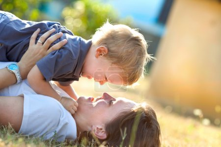 beautiful blonde child play with his mum outdoor