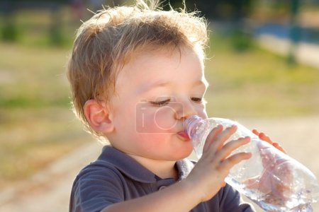 Photo for Beautiful blonde child drink water outdoor - Royalty Free Image