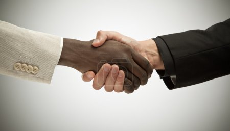 black and white interracial handshake isolated on grey