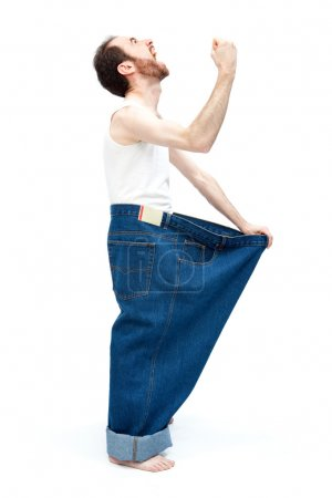 funny slim man with large pants jeans isolated on white