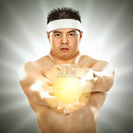 asian body builder with energy in his hands on grey background