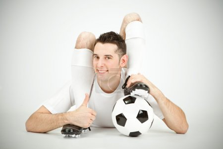 Contorsionist flexible soccer football player thumb up ball under foot on grey background