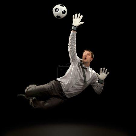 businessman goalkeeper save a goal on black background