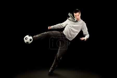 young businessman plays soccer football on black background