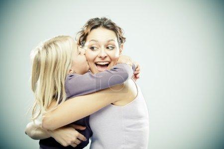 Photo pour Belle femme brune avec jeune fille blonde sur fond gris - image libre de droit