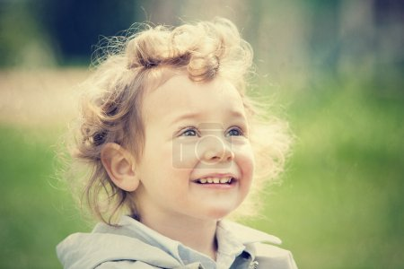Photo pour Beau blond bouclé cheveux enfant jouer en plein air dans un parc - image libre de droit