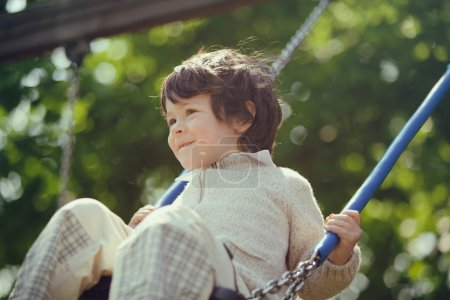 beautiful male kid play on swing in a park