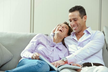 young happy couple relax on couch at home