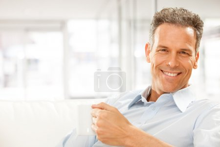 Handsome smiling businessman drink cup of tea at office