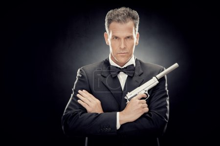 elegant man with bow tie and gun isolated on black