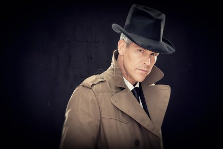 Handsome businessman with hat and raincoat isolated on black