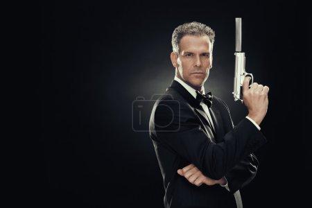 Photo pour Homme élégant avec nœud papillon et pistolet isolée sur fond noir - image libre de droit