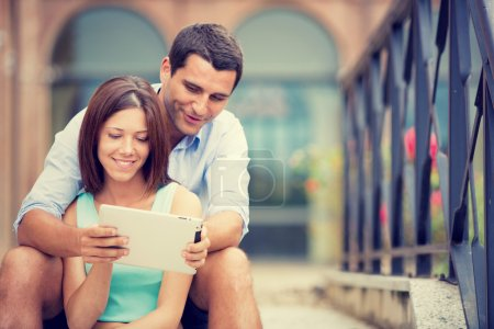 young brunette couple having fun together with tablet at park