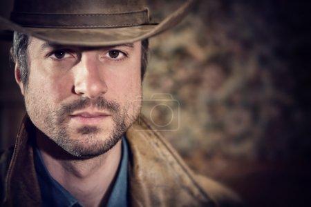 Photo pour Cow-Boy beau regard sensuel et chapeau dans une vieille maison - image libre de droit