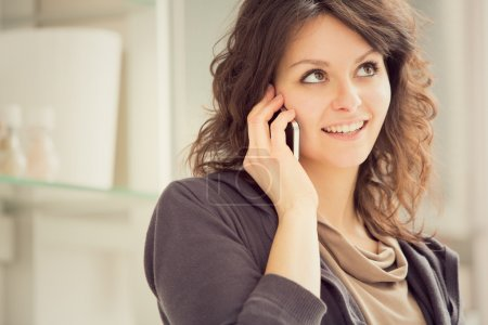 Young smiling brunette woman with phone in the kitchen