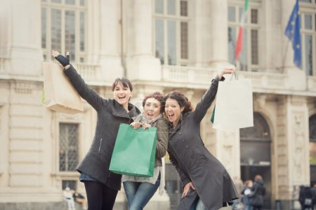 smiling happy women shop together in cityscape