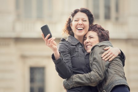 couple of smiling women take selfie in cityscape