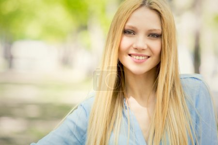 Photo for Smiling blonde young woman portrait in a green cityscape - Royalty Free Image