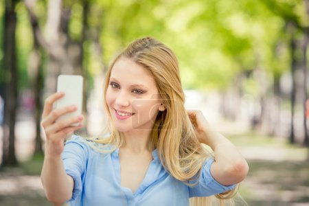 smiling blonde young woman with phone portrait in a green cityscape