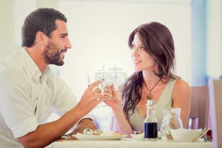 Photo for Young romantic couple drink to each other at restaurant - Royalty Free Image