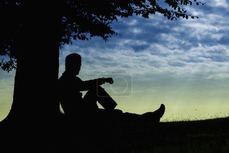 Photo pour Silhouette homme assis sous l'arbre par temps nuageux en plein air - image libre de droit